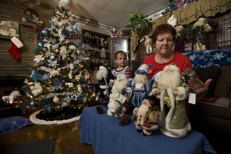 Deborah Ludwig sits beside a table of Santa Claus decorations in her Strasburg home with her grandson William Ludwig, 4. Ludwig has a collection of more than 450 Santas.  Rich Cooley/Daily